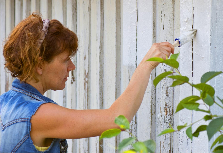 Kvinna som målaren en husfasad